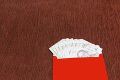 Rött kuvert med banken för thai baht som kinesisk för gåva` för nytt år ` för angpao, Royaltyfri Fotografi