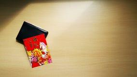 Rött kuvert och en svart plånbok Arkivfoton