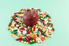 Rött - läckert äpple på en hög av preventivpillerar eller minnestavlor royaltyfri foto