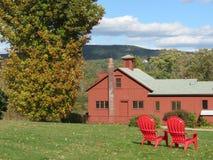 Rött lantgårdhus på ett fält av gräs Royaltyfri Fotografi