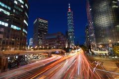 Rött ljus skuggar från strimma för medeltrafik över en upptagen genomskärning framme av Taipei 101 Arkivbilder