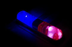 Rött ljusblinker uppe på av en polisbil Stadsljus på bakgrunden Polisregeringbegrepp Royaltyfri Bild