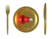 Rött ljuskula, guld- platta, gaffel och kniv. Bästa sikt Arkivbilder