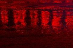 Rött ljusreflexioner på en våt väg Royaltyfria Foton