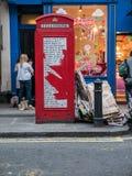 Rött London telefonbås med gatapoesi Arkivfoto