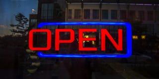 Rött och blått öppet tecken på en reflecive glass dörr royaltyfri foto