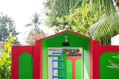 Rött och grönt hus med en blå stege inom royaltyfri fotografi