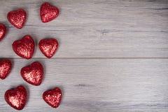 Rött och vitt blänka hjärtor på träbakgrund Royaltyfri Fotografi