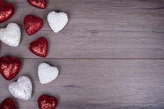 Rött och vitt blänka hjärtor på träbakgrund Royaltyfria Bilder