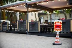 Rött och vitt förbjudas inget parkeringstecken, i ryskt och rumänskt, bilar från terrassen av restaurangen, plast- tecken arkivbild