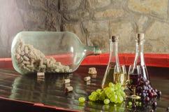 Rött och vitt vin med exponeringsglas och grupper av druvor royaltyfri foto