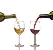 Rött och vitt vin som hälls in i vinexponeringsglas på den vita backgroen Arkivbild