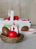 Rött påskägg, chokladägg och dekorativ höna i rede på träbakgrund Royaltyfria Bilder