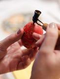Rött påskägg i förlagehänderna Arkivfoto