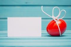 Rött påskägg med den vita pilbågen på blå träbakgrund med det tomma kortet royaltyfri bild