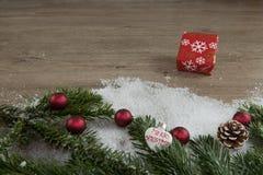 Rött paket i snön och röda julbollar Fotografering för Bildbyråer