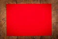 Rött papper som bakgrund på trätabellen Arkivfoto