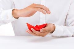 Rött pappers- fartyg i den manliga handen på vit bakgrund arkivfoto