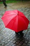 Rött paraply i regnig dag Arkivfoto