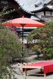 Rött paraply i trädgård Arkivfoto