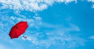 Rött paraply med blå himmel Arkivfoto