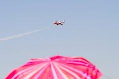 Rött paraply och militärflygplan Royaltyfri Bild
