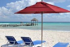 Rött paraply och sunbeds på stranden Arkivbilder