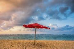 Rött paraply på en strand Fotografering för Bildbyråer