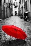 Rött paraply på kullerstengatan i den gamla staden Vind och regn arkivbilder