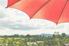 Rött paraply under himmel Fotografering för Bildbyråer