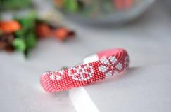 Rött prytt med pärlor virkat armband med det blom- trycket royaltyfri bild