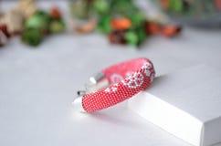 Rött prytt med pärlor virkat armband med det blom- trycket royaltyfria foton