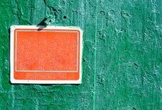 Rött rostigt grungy gammalt plast- tecken på en cementvägg Arkivbild