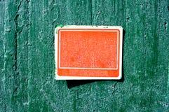 Rött rostigt grungy gammalt plast- tecken på en cementvägg Fotografering för Bildbyråer