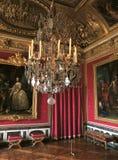 Rött rum med stora målningar och ljuskrona på den Versailles slotten, Frankrike Royaltyfri Bild
