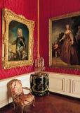 Rött rum, stora målningar och fåtöljer på den Versailles slotten Arkivfoto