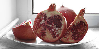 Rött saftigt moget granatäpplesnitt in i stycken på en vit bakgrund på tefatet Arkivbild