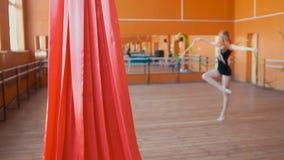 Rött siden- framme av den unga kvinnan som utbildar en gymnastikövning med ett band Arkivbilder
