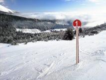 Rött skidar tecknet för rutt 1 på ny snö med den snö täckte skogen arkivbilder