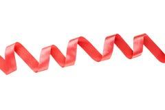 Rött skinande satängband på vit bakgrund Arkivfoto