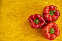 Rött slut för spansk peppar tre upp på trägul bakgrund med kopieringsutrymme på vänstra sidan Spanska peppar på trägul textur Fotografering för Bildbyråer