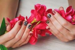 Rött spika konst med utskrivavna blommor på träbakgrund Royaltyfria Foton