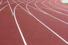 Rött sportspår för att köra på stadion med vita linjer Rinnande sunt livsstilbegrepp Sportbakgrundsabstrakt begrepp royaltyfri foto