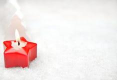 Rött stearinljus i snowen arkivbilder