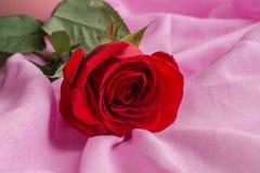 Rött steg ligga på pastellfärgad rosa textur av tyget Valentindag, moderdag, kvinnors dagbegrepp arkivfoton