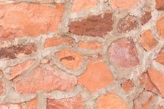 Rött stena utomhus- bakgrund för väggen, och textur av dekorativt kritiserar stenen royaltyfria bilder