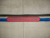 Rött stiga ombord zontecken på betongväggen i gångtunnelstation royaltyfria bilder