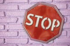Rött stopptecken på den rosa väggen Royaltyfri Fotografi