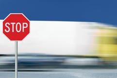 Rött stoppvägmärke, för lastbilmedel för rörelse suddig trafik i bakgrund, reglerande varningssignageoktogon, vit åttahörnig ram arkivfoton