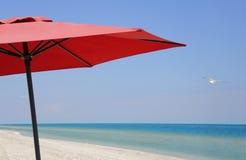 Rött strandparaply på en solig dag Arkivfoto